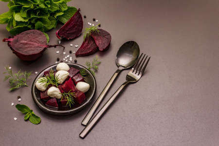 Culinary background. Cooking food concept. Healthy salad with baked beetroot, baby mozzarella, fresh greens. Trendy black stone concrete backdrop, copy space