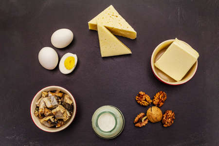 Foods containing vitamin D. Cheese, eggs, butter, nuts, milk, sardine. Black chalk board background