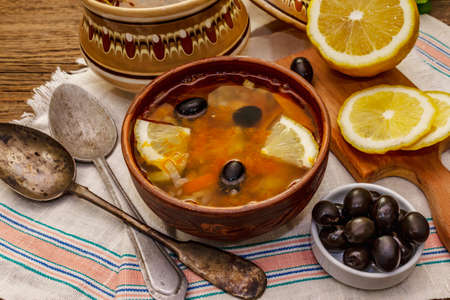 Hodgepodge, hot soup served in traditional ceramic bowl and pot. Classical Eastern Europe dish, old vintage wooden boards background
