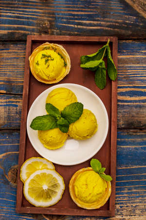Lemon ice cream with mint. Refreshing summer dessert, ripe fruit, fragrant leaves. Wooden boards background, top view