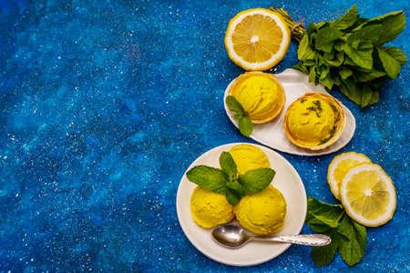 Lemon ice cream with mint. Refreshing summer dessert, ripe fruit, fragrant leaves. Navy blue nautical background, top view
