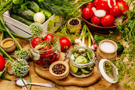Pickling vegetables concept. Cooking process, spices, fresh fragrant herbs. Ripe tomatoes and cucumbers, old wooden table