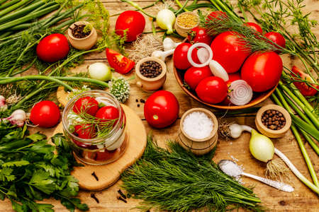 Pickling vegetables concept. Cooking process, spices, fresh fragrant herbs. Ripe tomatoes, old wooden table