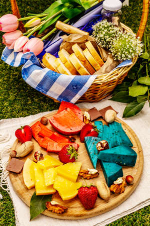 Picnic concept. Assorted multicolored hard Dutch cheeses. Blue and red pesto, aged gouda. Strawberry, chocolate, nuts, herbs, juice and wine. Wicker basket on green grass background, close up