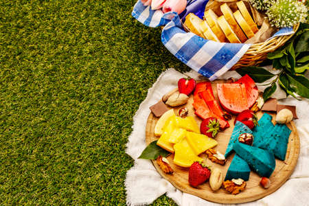 Picnic concept. Assorted multicolored hard Dutch cheeses. Blue and red pesto, aged gouda. Strawberry, chocolate, nuts, herbs, juice and wine. Wicker basket on green grass background, copy space