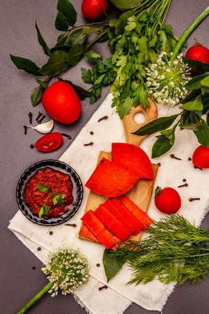 Dutch gouda pesto red cheese. Ripe tomatoes, fresh herbs, fragrant spices. Black stone concrete background, close up