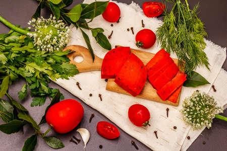 Dutch gouda pesto red cheese. Ripe tomatoes, fresh herbs, fragrant spices. Black stone concrete background, top view