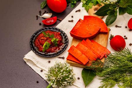 Dutch gouda pesto red cheese. Ripe tomatoes, fresh herbs, fragrant spices. Black stone concrete background, copy space Фото со стока
