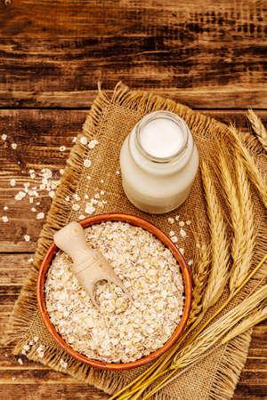 Vegan oat milk, non dairy alternative milk. Dry flakes in ceramic bowl, glass bottle, oats. Vintage wooden background, close up