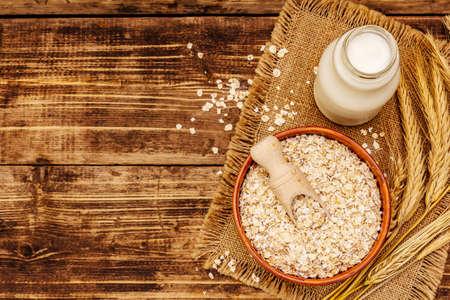 Vegan oat milk, non dairy alternative milk. Dry flakes in ceramic bowl, glass bottle, oats. Vintage wooden background, top view Stock fotó
