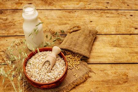 Vegan oat milk, non dairy alternative milk. Dry flakes in ceramic bowl, glass bottle, oats. Vintage wooden background, copy space