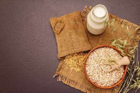 Vegan oat milk, non dairy alternative milk. Dry flakes in ceramic bowl, glass bottle, oats. Black stone concrete background, top view