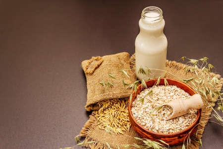 Vegan oat milk, non dairy alternative milk. Dry flakes in ceramic bowl, glass bottle, oats. Black stone concrete background, copy space Stock fotó