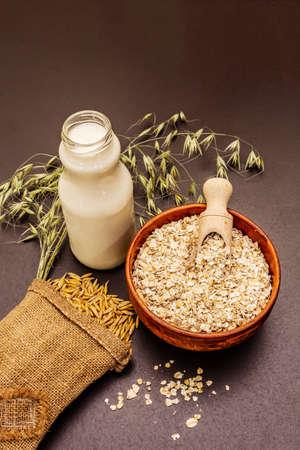Vegan oat milk, non dairy alternative milk. Dry flakes in ceramic bowl, glass bottle, oats. Black stone concrete background, close up