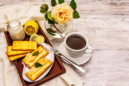 Healthy breakfast. Cup of coffee (black tea), milk, crackers with butter and salmon. Morning good mood, old wooden background, copy space