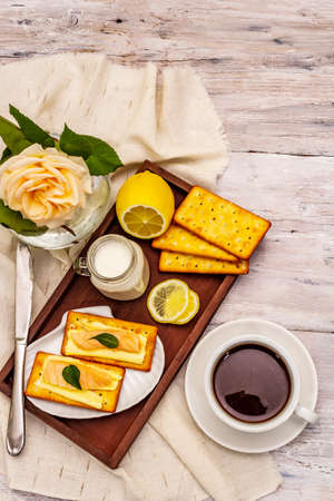 Healthy breakfast. Cup of coffee (black tea), milk, crackers with butter and salmon. Morning good mood, old wooden background, top view