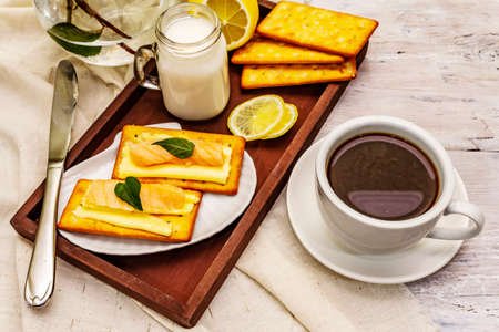 Healthy breakfast. Cup of coffee (black tea), milk, crackers with butter and salmon. Morning good mood, old wooden background, close up