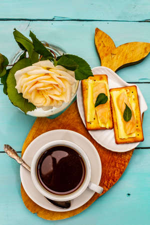 Healthy breakfast. Cup of coffee (black tea), milk, crackers with butter and salmon. Morning good mood, turquoise wooden background, top view