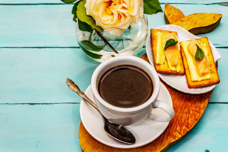 Healthy breakfast. Cup of coffee (black tea), milk, crackers with butter and salmon. Morning good mood, turquoise wooden background, copy space