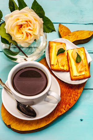 Healthy breakfast. Cup of coffee (black tea), milk, crackers with butter and salmon. Morning good mood, turquoise wooden background, close up
