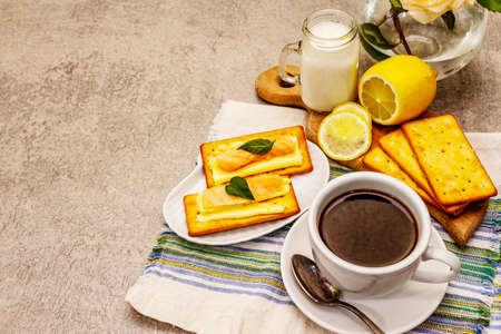 Healthy breakfast. Cup of coffee (black tea), milk, crackers with butter and salmon. Morning good mood, stone concrete background, copy space Banco de Imagens