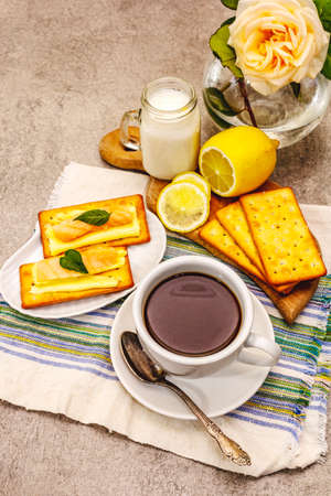 Healthy breakfast. Cup of coffee (black tea), milk, crackers with butter and salmon. Morning good mood, stone concrete background, close up