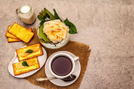 Healthy breakfast. Cup of coffee (black tea), milk, crackers with butter and salmon. Morning good mood, stone concrete background, top view