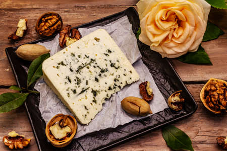Cheese with blue mold. Ingredient for a cheese plate. Nuts, fragrant bay leaves, knife. Wooden boards background, close up Imagens