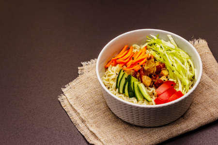 Traditional Korean noodle bowl with smoked chicken, fresh sliced vegetables and sesame seeds. Trendy black stone concrete background, copy space Banque d'images
