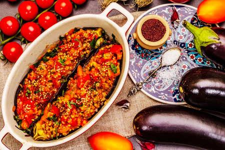 Karniyarik traditional Turkish food. Stuffed eggplants with minced meat, tomato, greens and sesame seeds. Black stone concrete background, top view