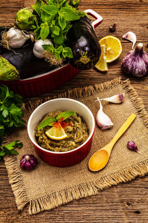 Eggplant dip baba ganoush (mutabbal) or mezze with ripe vegetables and fresh herbs. Traditional Middle East cuisine, healthy appetizer, vegan hummus. Old wooden boards background, close up Zdjęcie Seryjne