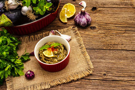 Eggplant dip baba ganoush (mutabbal) or mezze with ripe vegetables and fresh herbs. Traditional Middle East cuisine, healthy appetizer, vegan hummus. Old wooden boards background, copy space Zdjęcie Seryjne