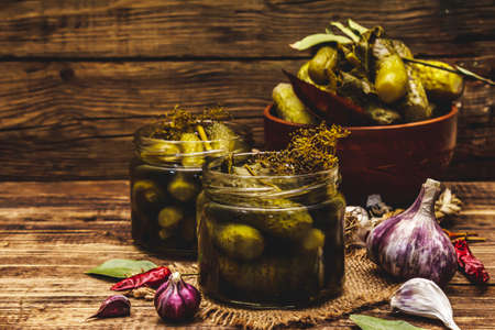 Marinated pickled cucumbers with spices and herbs. Traditional fermented appetizer in glass jars and clay bowl. Wooden boards background, copy space