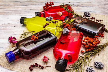 Homemade assortment of berries liqueurs or tincture. Sweet mountain fruits, fragrance herbs, glass bottles. White old wooden boards background, close up Фото со стока