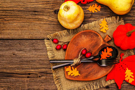 Autumn table setting. Thanksgiving or Halloween concept. Leaf-shaped ceramic plate, black cutlery, pumpkins and dog rose berries. Old wooden boards background, top view Standard-Bild