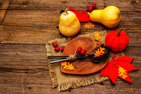 Autumn table setting. Thanksgiving or Halloween concept. Leaf-shaped ceramic plate, black cutlery, pumpkins and dog rose berries. Old wooden boards background, copy space