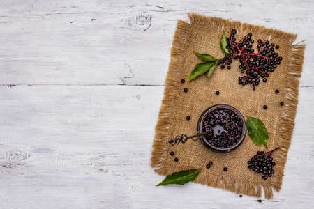 Elderberry jam. Ripe berries, sweet and healthy dessert. Alternative medicine and lifestyle. White wooden boards background, top view