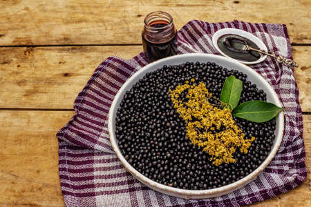Elderberry jam, syrup or confiture. Fresh ripe berries, healthy sweet dessert. Alternative medicine and lifestyle. Old wooden table, copy space Фото со стока