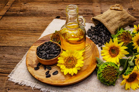 Sunflower oil in glass cruet with flower head and seeds in wooden bowl. Vintage wooden boards background, rural still-life, close up
