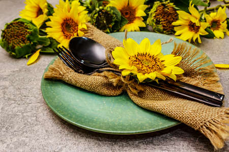 Autumn and Thanksgiving dinner place setting. Sunflower bouquet, ceramic plate and sackcloth napkin. Fall black cutlery on stone concrete background, close up