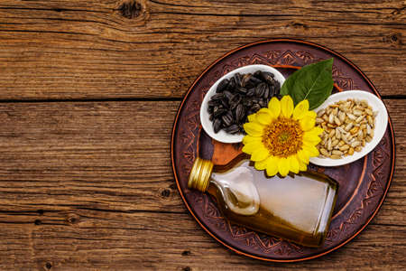 Sunflower oil in glass cruet with flower head and seeds in bowls. Vintage wooden boards background, rural still-life, top view