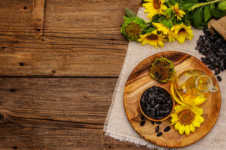 Sunflower oil in glass cruet with flower head and seeds in wooden bowl. Vintage wooden boards background, rural still-life, top view