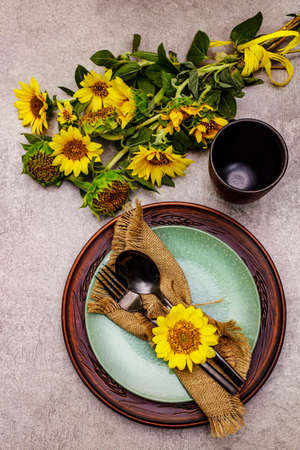 Autumn and Thanksgiving dinner place setting. Sunflower bouquet, ceramic plates and sackcloth napkin. Fall black cutlery on stone concrete background, close up