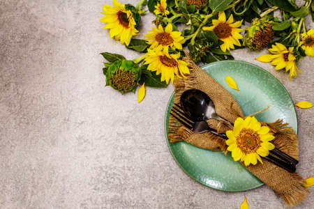 Autumn and Thanksgiving dinner place setting. Sunflower bouquet, ceramic plate and sackcloth napkin. Fall black cutlery on stone concrete background, top view