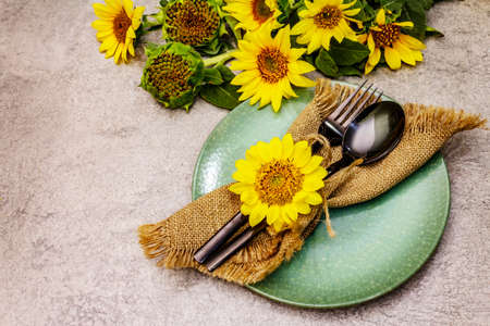Autumn and Thanksgiving dinner place setting. Sunflower bouquet, ceramic plate and sackcloth napkin. Fall black cutlery on stone concrete background, copy space