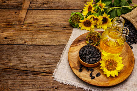 Sunflower oil in glass cruet with flower head and seeds in wooden bowl. Vintage wooden boards background, rural still-life, copy space