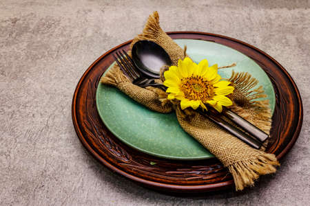 Autumn and Thanksgiving dinner place setting. Sunflower bouquet, ceramic plates and sackcloth napkin. Fall black cutlery on stone concrete background, copy space
