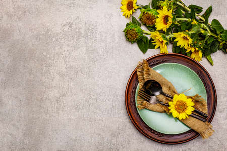 Autumn and Thanksgiving dinner place setting. Sunflower bouquet, ceramic plates and sackcloth napkin. Fall black cutlery on stone concrete background, top view Фото со стока
