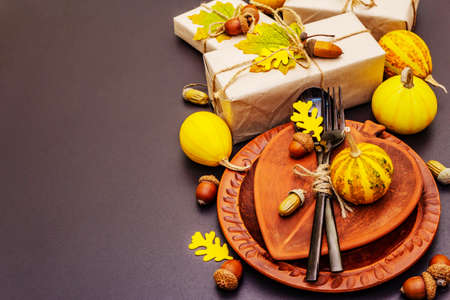 Autumn table setting. Thanksgiving or Halloween concept. Crafted gift boxes, fall decor and black cutlery. Stone concrete background, copy space