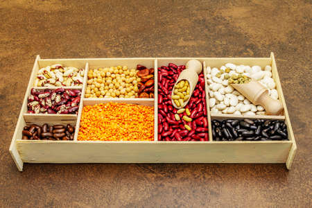 Set of various dry legumes in wooden box, indispensable protein for a healthy lifestyle. Assorted different types of beans. Stone concrete cooking background, close up